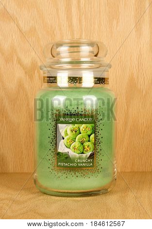 RIVER FALLS,WISCONSIN-MAY 03,2017: A pistachio scented candle jar with a wood background.
