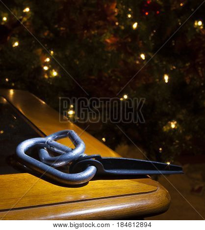 Pair of old carabiners and piton with a lit Christmas tree behind