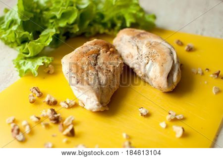 Ruddy Chicken Breasts With Leaf Salad And Crushed Walnut On Yellow Cutting Board.