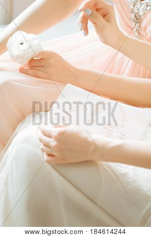Blurred image in pink beige pastel colors background two tender girls morning bride read letter calligraphy. Boudoir photography. Selective focus. High key