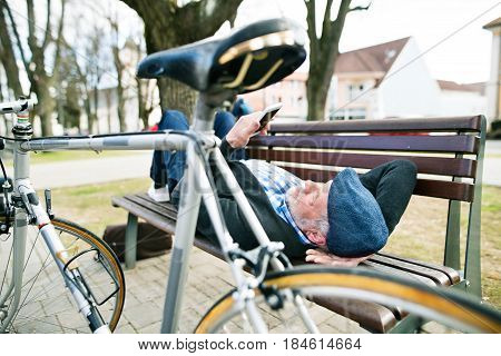 Handsome senior man with bicycle in town park lying on bench, holding smart phone, texting. Sunny spring day.
