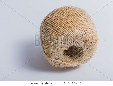 Ball of cotton brown twine on white background