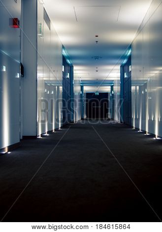 Interior of hotel hallway lite up to the elevator