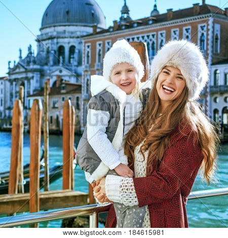 Mother And Daughter Standing On Embankment In Venice
