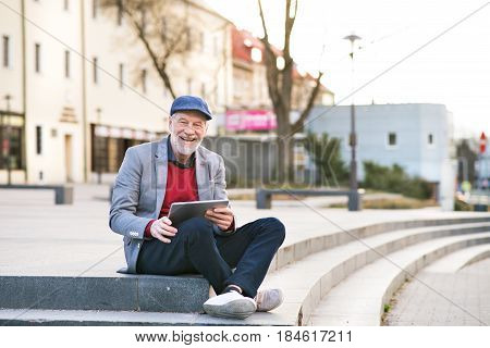 Handsome senior man in town sitting on stairs, holding laptop, smiling. Sunny spring day.