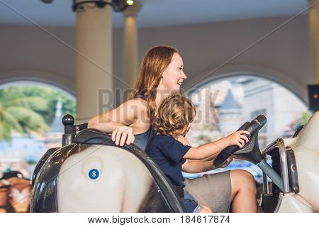 Mom And Son Having A Ride In The Bumper Car At The Amusement Park