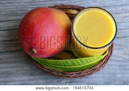 Fresh mango smoothie,ripe mango fruit and mango tree leaf on old wooden table background.Healthy food,diet or vegan food concept.Top view.