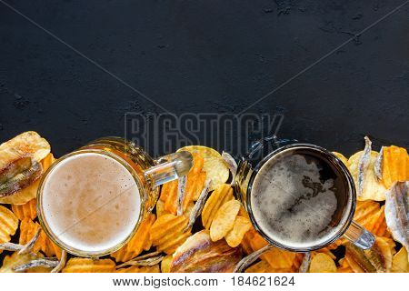 Two Mugs Of Beer, Chips And Fish On A Black Background With Space For Text