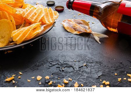 Bottle Of Beer, Chips And Fish On A Black Background
