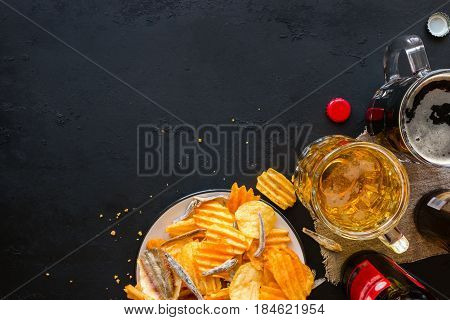 Light And Dark Beer With A Snack Of Chips And Fish On A Black Background Mockup