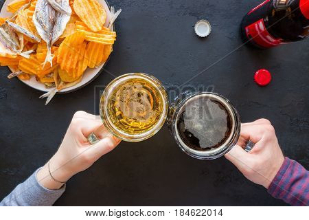 People Keep Mugs With Dark And Light Beer On The Background Of Snacks Of Chips And Fish