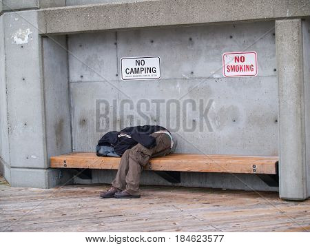 Seattle, USA - July 20, 2008; Person asleep wearing old clothes on public bench in public place under no camping and no smoking signs