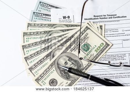 Close up image of money,$100 bills,W-9 form,glasses and a pen on white background