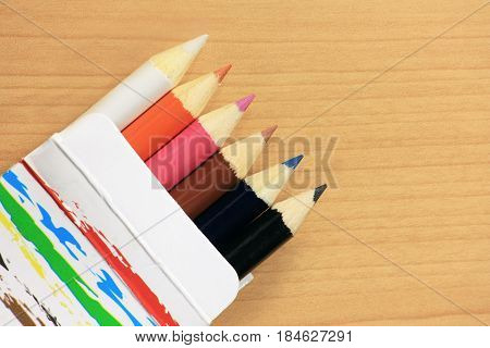 Colorful pencils in paper box on wood