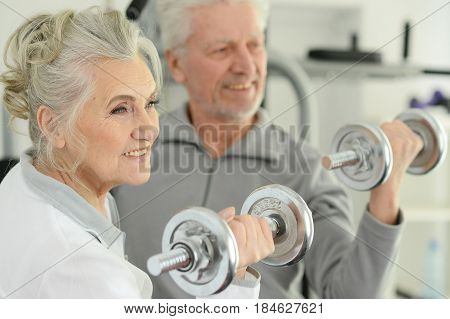 Beautiful elderly couple in a gym with dumbbells