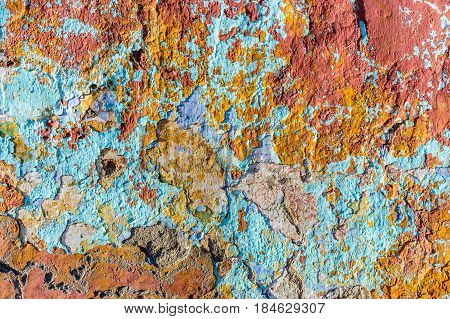 Close up of chipped peeling colorful paint on old wall