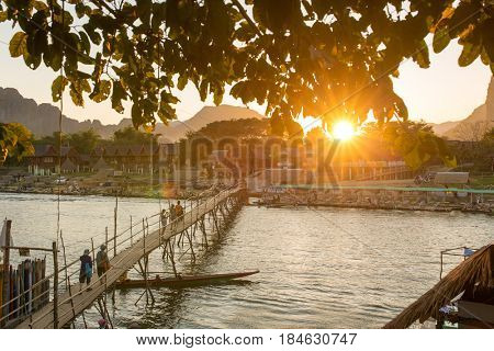 Vang Vieng, Laos - January 19, 2017: Wooden bridge across Nam Song river during sunset in Vang Vieng village, Laos
