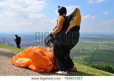 Paraglider sportman prepares to jump under blue summer sky