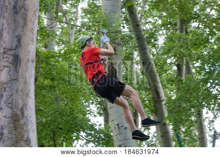 young man on zipline in adventure park in forest