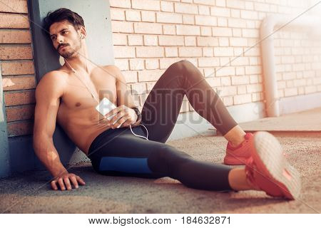 Portrait of handsome young man listening to music after running.