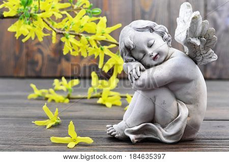 Angel guardian and spring flowers on wooden background