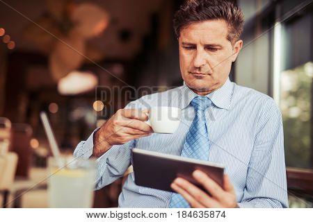 Attractive mid adult man drinking coffee in cafe and using his digital tablet.