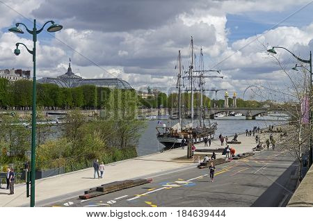 PARIS FRANCE - APRIL 1 2017: People walk along the Seine River embankment on weekend. The beginning of April. Paris France.