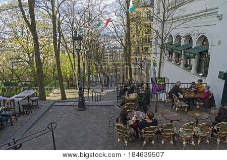 PARIS FRANCE - APRIL 1 2017: A small cafe (Irish pub) on the stairs leading to the top of the hill of Montmartre. Paris France early April evening.