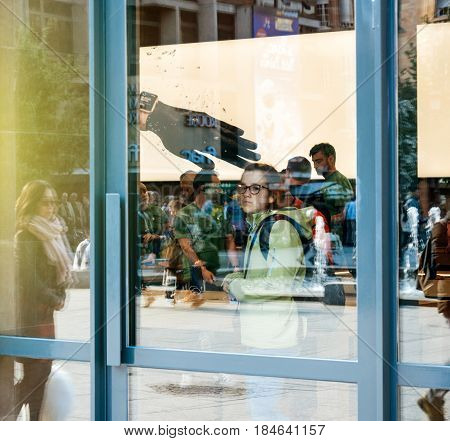 STRASBOURG FRANCE - APR 23 2017: Young girl seen through glass window facade of the Apple Store interior with customers buying diverse computers smartphones and gadgets