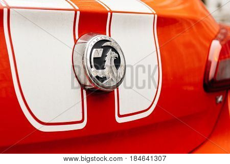 LONDON UNITED KINGDOM - MAR 11 2017: Vauxhall logotype insignia on a red sport car with white stripes. The Vauxhall logo is based on a mythical creature called the