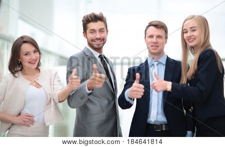 Business colleagues looking at camera and shoving thumbs up in t