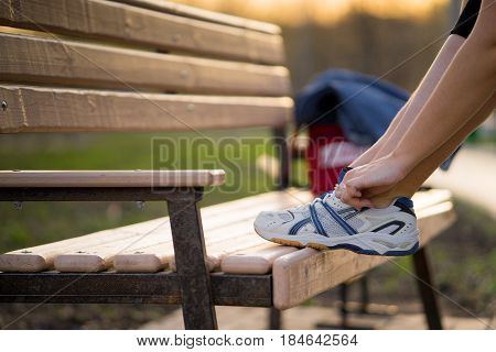 woman tying shoelace outdoor. girl ties the laces shoes. foot on the bench