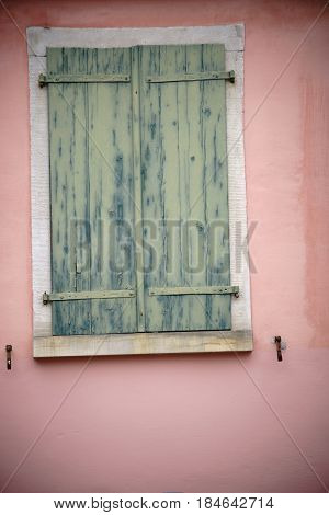An old wooden and fading closed window shutter on a nostalgic window.