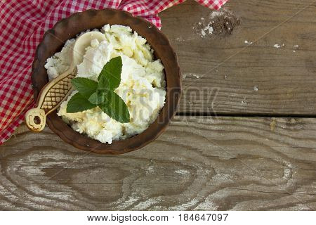 dairy product cottage cheese in brown ceramic bowl. Curd in brown bowl on red napkin. Fresh cottage cheese in bowl with spoon on vintage wooden tabledoor