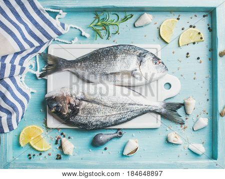 Fresh Sea bream or dorado raw uncooked fish with seasoning on white board over turquoise blue tray background, top view