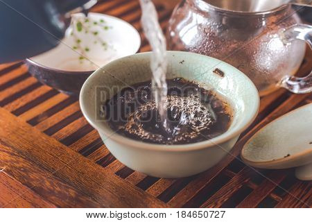 Pouring Chinese Shen Puerh tea from a teapot into a cup or Gaiwan on a wooden traditional tea table with other utensils on background