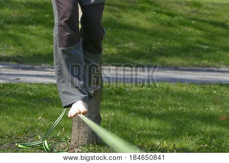 Barefoot Slackline Walker In A Park With Green Grass