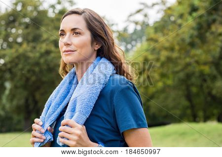Beautiful fit mature woman resting after workout. Proud brunette woman relaxing with blue towel around neck after yoga in park. Thoughtful mid adult woman thinking after sport and looking away.