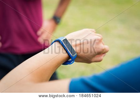 Close up of woman arm with sports watch. Woman using smart watch outdoor. Woman checking fitness and health tracking wearable device. Female runner looking app on sportwatch.