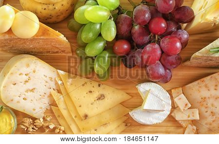 Different types of cheese with grapes on wooden table