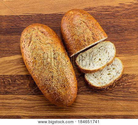Loaf of wholegrain white bread and slices on wooden background
