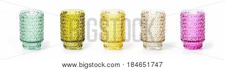 Colorful glass jars could be used as candlesticks over white background