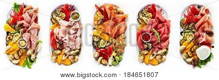 Selection of different kinds of meat and sausage with grilled vegetables and mushrooms. Range of plates over white background.