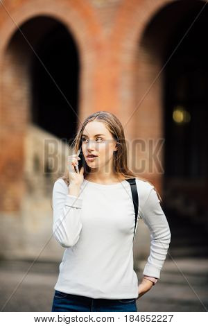Happy Student Girl Walking And Calling On Mobile Phone Outdoors With A Uni Background
