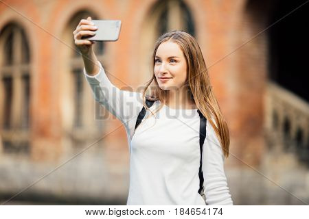 Girl College Student Sitting Outside Building And Taking A Selfie On Campus Background