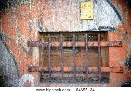 The closeup of a colorful painted basement of glass tiles with rusted iron bars.