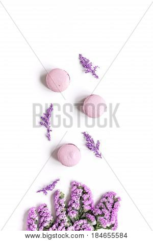 spring woman breakfast with macaroons and mauve flowers white background top view space for text