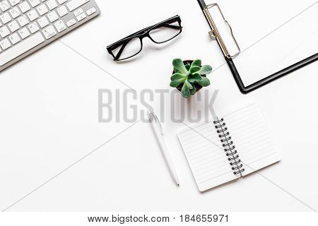 Workspace with glasses and notebook on office desk white background top view mock up