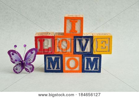 I love mom spelled with colorful alphabet blocks and a purple silk butterfly