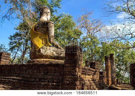 Wat Khao Phanom Phloeng stature buddha and blue sky in Sisatchanalai Historical Park Sukhothai province Thailand